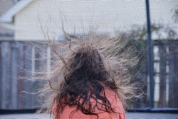 A girl sitting inside a trampoline with netted barrier. Static electricity rising hair up in the air