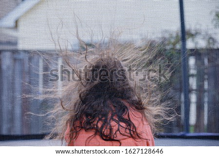 Photo of  A girl sitting inside a trampoline with netted barrier. Static electricity rising hair up in the air