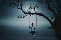 A girl sitting on a swing, watching the full moon by the sea