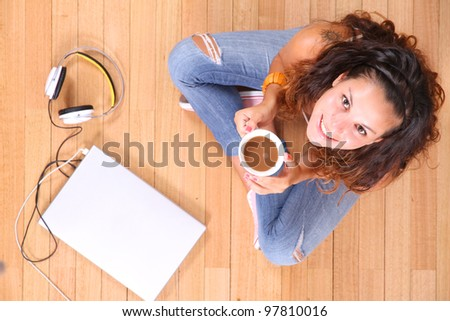 A girl sitting on the floor with a Laptop and some coffee.