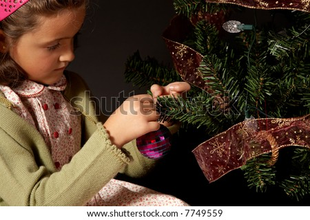 A girl small girl settiing up a christmas tree