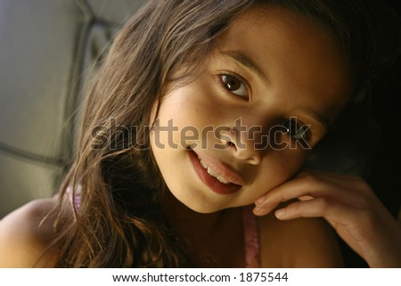 A girl smiles happily in the warm glow of the evening sun