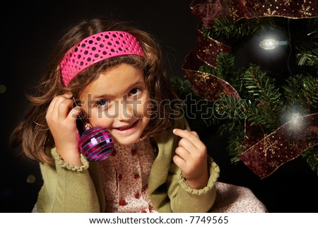 A girl smiling nearby a christmas tree holding a christmas ball.