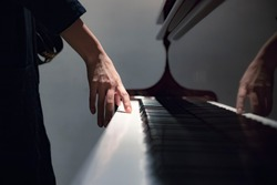 a girl standing next to an old classic piano touching the keys with her hand, a girl playing the piano close up blurred
