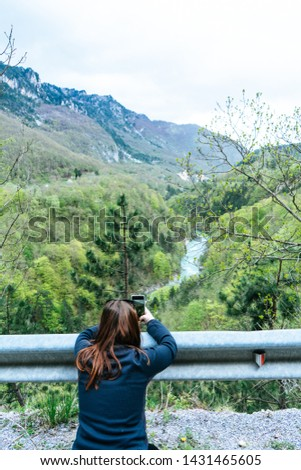 A Girl Standing on the Cliff and Taking Photograph of the Valley with the River. Red head making picture with smart phone to Tara River in Durmitor