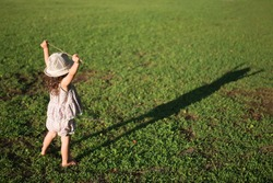 a girl standing on the grass looking at his shadow