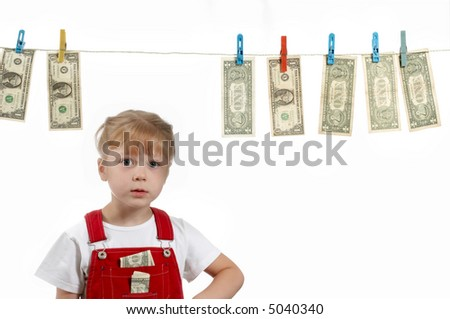 A girl standing under clothesline with dollars