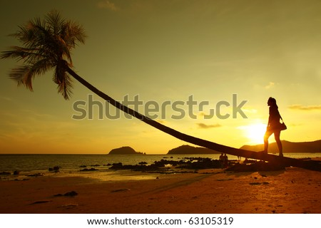 A girl stands by the palm tree on the beach at sunset , Thailand, Asia