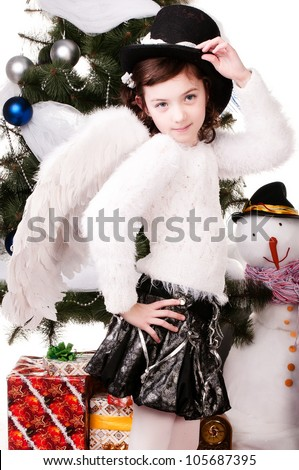 A girl stands near a Christmas tree, a beautiful girl in angel costume with hat