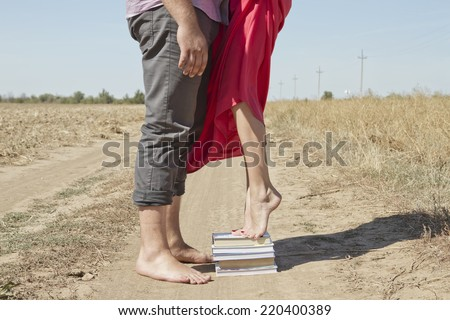 A girl stands on a stack of books to reach out and kiss the guy #220400389