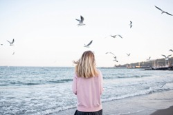 A girl stands on the beach and seagulls are flying nearby. Enjoy the moment. Rest and relaxation by the sea. Weekend in nature. Life style