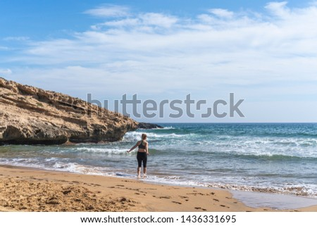 A girl stands on the edge of the surf in a beautiful sandy cove edged with sedimentary rock cliffs, part of the Calblanque Regional Park, Murcia, Spain. The mediterranean sky is blue with clouds.