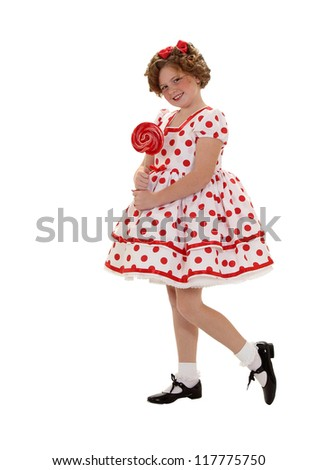 A girl stands with a red lollipop in a polka dot dress isolated on white