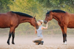 A girl stroking horses, kisses a horse in the face. A man with horses free.