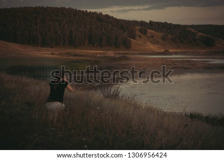 a girl takes a pic of landscape of lake and forest near village