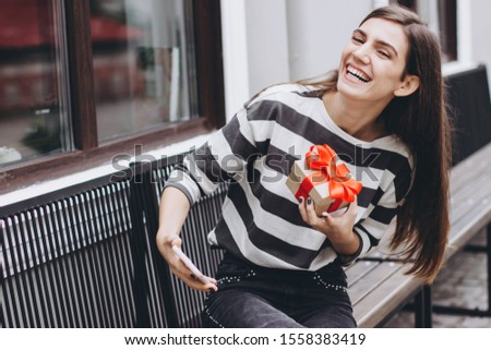 A girl takes a selfie on her smartphone in a light silicone case. Cheerful girl takes a selfie with a gift holding a box with a bow. Selective focus.