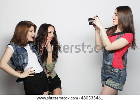 A girl takes picture of her friends. Concept of friendship and fun.Best friends enjoying the moment with modern camera.