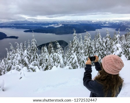 A girl taking a picture atop Cypress Mountain overlooking the ocean below. In the distance hikers and snowshoers can see Howe Sound, Sunshine Coast, Bowen and Gambier Island, and the Coast Mountains.