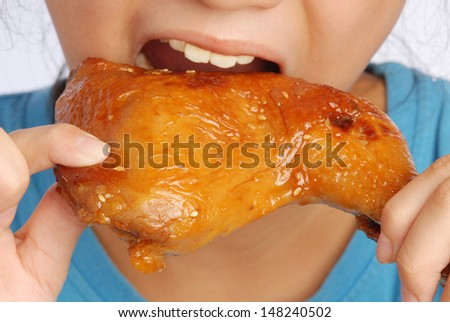 A girl tasted roasted chicken leg drumstick