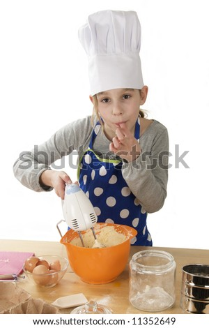 a girl tasting cake batter and using a mixer