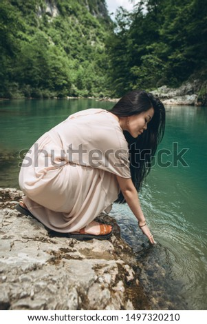 A girl touches the water in a river or pond or lake. Unity with nature.