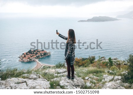 A girl tourist or a blogger takes a selfie or takes photos or videos of a beautiful view in Montenegro.