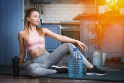 A girl trains at home with a bottle of water. Home training with weights. Canister for exercise. A woman plays sports in an apartment. Isolation during the virus. Healthy lifestyle.