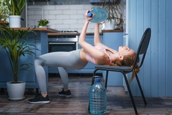 A girl trains at home with a bottle of water. Home training with weights. Canister for exercise. A woman plays sports in an apartment. Isolation during the virus. Exercises for the upper body.