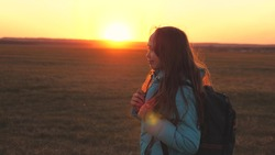 A girl traveler walks with a backpack on her back and smiles at the sunset in the sky. A teenager on a camping trip on vacation. Childhood in search of adventure from morning to dawn. Love for the