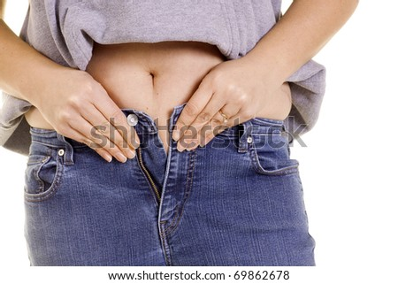 A girl tries to squeeze into jeans that are too tight.