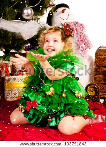 A girl under the Christmas tree with gifts, the girl is happy snowfall and catches it with his hands