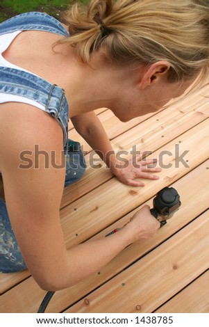 A girl uses an air gun to nail her new deck.