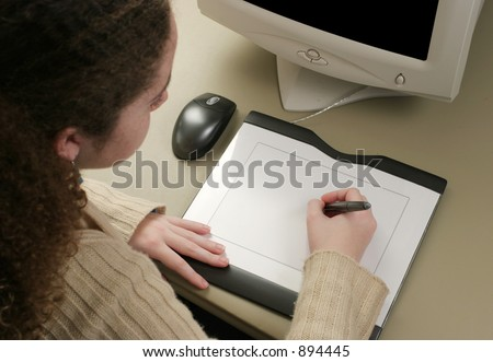A girl using a graphic tablet to draw on the computer.