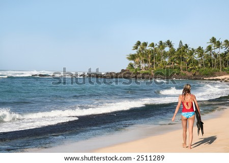A girl walking on the beach with a bodyboard