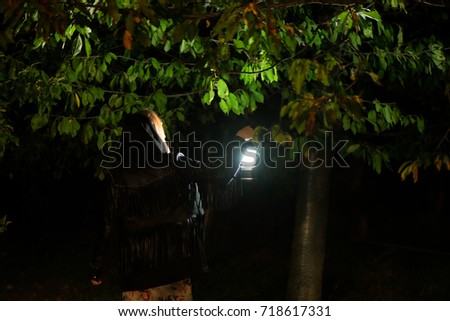 Stock Photo A girl walking through the woods with a dim light