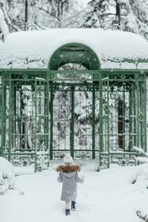 A girl walks along on a snow-covered path in the park during a snowfall. Snow on the branches of trees and wrought iron pavilion. Cold snowy winter weather. Vertical image.