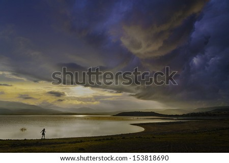 A girl walks along the shore of a lake as a large storm comes in. Sardinia Italy/stormy skies on a lake