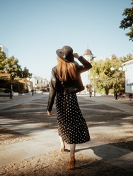 A girl walks in a dress with peas on the streets of Europe. Black hat, black leather jacket. Rear view. Beautiful view on the street