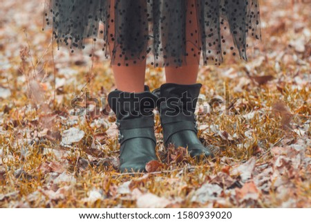 A girl walks in the park. Photo of female legs in black boots and a black skirt