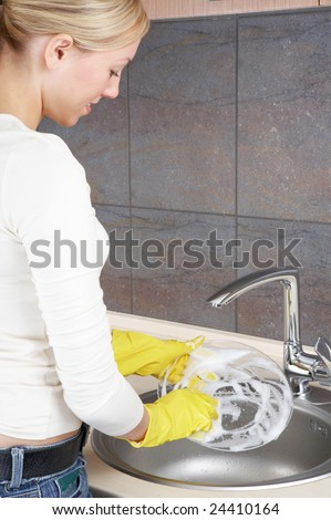 A girl washes a dish on a kitchen