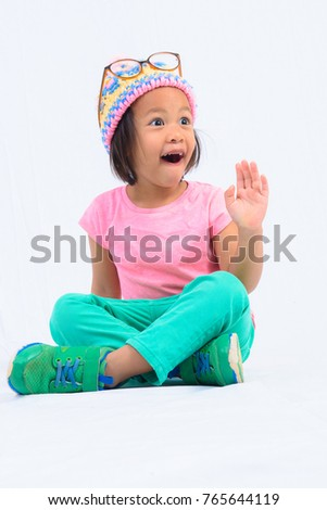 A girl wearing a pink sweater wears a hat on a white background. #765644119
