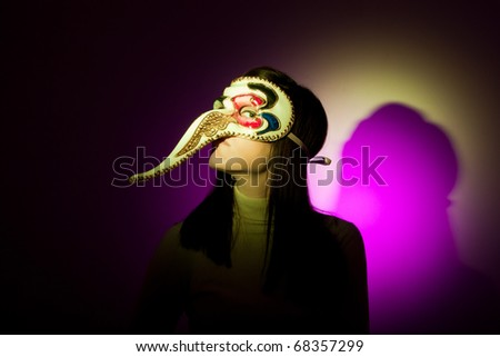 A girl wearing a venetian mask featuring a large nose, looking at camera. Illuminated using yellow and magenta spotlights.