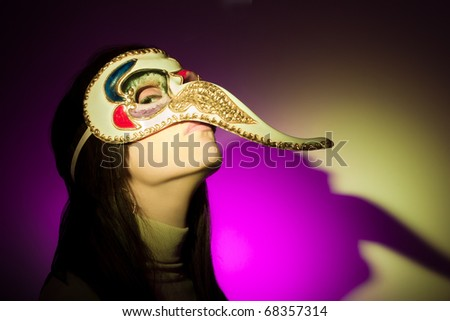 A girl wearing a venetian mask featuring a large nose, looking at camera. The shadow of her face (plus the mask's nose) is projected on the background. Illuminated using yellow and magenta spotlights.