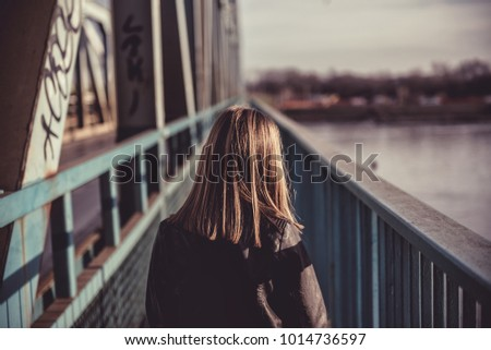 A girl wearing black leather jacket walking across the freight bridge over river Danube