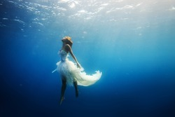 A girl wearing fashion white dress underwater in blue deep. A Wild Ocean Scenery without fish.