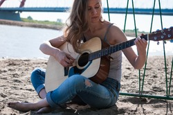 A girl wearing jeans and long hair sitting on the beach and the guitar