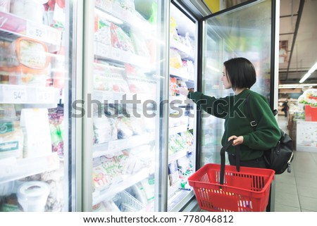 A girl with a basket takes frozen foods from the supermarket's refrigerator. The girl chooses goods in the store. Shopping in the supermarket.