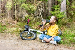 A girl with a bicycle sits on a path in a park or forest, drinks water from a bottle.