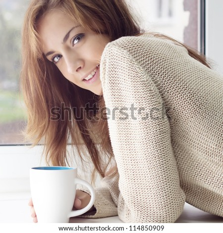 A girl with a charming smile and a glass on a window