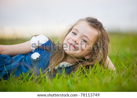 A girl with a cheeky smile relaxing on the green grass